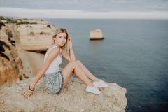 Belle femme de pensée s'asseyant sur la pierre sur le fond bleu d'océan et de ciel dans le coucher du soleil concept de course photographie stock