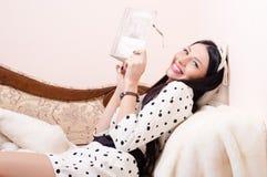 Belle femme de pin-up ayant l'appareil-photo de sourire de livre de lecture d'amusement et de regard heureux détendant sur l Image stock