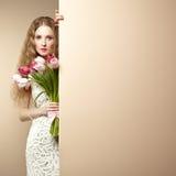 Belle femme de portrait avec le bouquet des fleurs Image stock