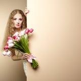 Belle femme de portrait avec le bouquet des fleurs Images stock