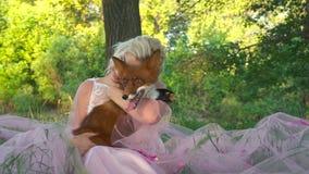 Belle femme de portrait tenant le renard rouge dans ses mains et sourire banque de vidéos