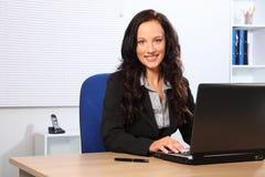 Belle femme de sourire à l'aide de l'ordinateur portatif dans le bureau Photographie stock