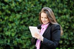 Belle femme de sourire à l'aide de la tablette Photographie stock libre de droits
