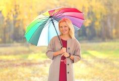 Belle femme de sourire avec le parapluie coloré dans le jour ensoleillé d'automne images stock