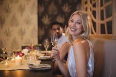 Belle femme de sourire avec le verre de champagne dans le restaurant Photographie stock libre de droits