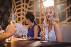 Belle femme de sourire avec le verre de champagne dans le restaurant Image libre de droits