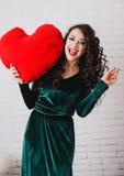 Belle femme de sourire avec les mains rouges de coeur la Saint-Valentin Photo stock