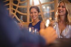 Belle femme de sourire ayant le verre de champagne dans le restaurant Photo libre de droits