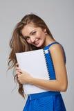 Belle femme de sourire d'affaires, avec des documents, sur un dos de gris Image libre de droits