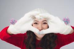 Belle femme de sourire dans la forme chaude de coeur de geste d'habillement Photographie stock libre de droits