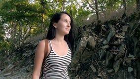 Belle femme de sourire de brune avec de longs cheveux marchant sur une route de montagne banque de vidéos