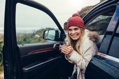 Belle femme de sourire en son café potable de voiture Photos stock