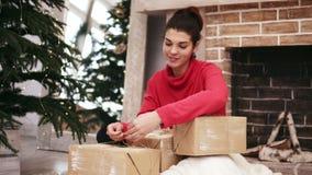 Belle femme de sourire enveloppant des cadeaux de Noël se reposant par l'arbre et la cheminée de Noël à la maison mettant alors clips vidéos