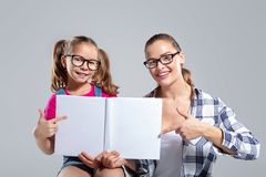 Belle femme de sourire et sa fille en verres avec le livre images stock
