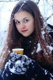 Belle femme de sourire heureuse d'hiver avec la tasse extérieure photos stock