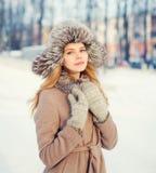 Belle femme de sourire heureuse utilisant un manteau et un chapeau au-dessus de neige en hiver Images libres de droits