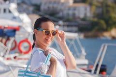 Belle femme de sourire marchant près de la marine de yacht Photos stock
