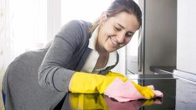 Belle femme de sourire nettoyant la fraise-mère électrique souillée sale sur la cuisine Image stock