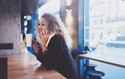 Belle femme de sourire s'asseyant au café urbain et parlant avec des amis par l'intermédiaire du smartphone mobile Portrait occas Photo stock