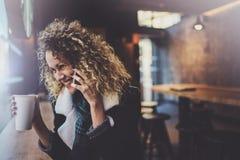 Belle femme de sourire s'asseyant au café urbain et parlant avec des amis par l'intermédiaire du smartphone mobile Portrait occas Image stock