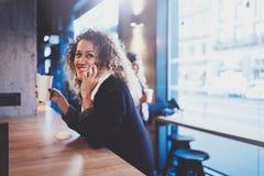 Belle femme de sourire s'asseyant au café urbain et parlant avec des amis par l'intermédiaire du smartphone mobile Portrait occas Photos stock