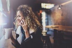 Belle femme de sourire s'asseyant au café urbain et parlant avec des amis par l'intermédiaire du smartphone mobile Portrait occas Image libre de droits
