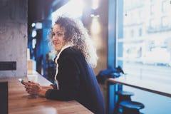 Belle femme de sourire s'asseyant au café urbain et parlant avec des amis par l'intermédiaire du smartphone mobile Portrait occas Photographie stock libre de droits