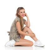 Belle femme de sourire s'asseyant sur un plancher Images libres de droits