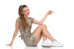 Belle femme de sourire s'asseyant sur un plancher et un pointage Photos stock