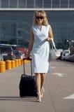 Belle femme de sourire se déplaçant avec une valise Photographie stock libre de droits
