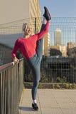 Belle femme de sourire soulevant sa jambe sur la rue photo libre de droits