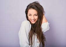 Belle femme de sourire toothy enthousiaste regardant avec heureux dans la chemise blanche avec la longue coiffure bouclée Vertica photos stock