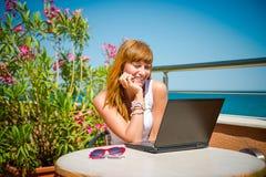 Belle femme de sourire travaillant sur l'ordinateur portable Photos stock