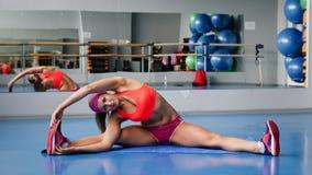 Belle femme de sport faisant étirant l'exercice de forme physique à la gymnastique de sport yoga Images stock