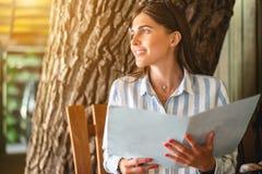 Belle femme de touristes dans le restaurant observant le menu images libres de droits