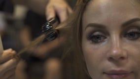 Belle femme de visage tout en redressant des cheveux dans le studio de coiffure Styliste en coiffure à l'aide du fer et du peigne banque de vidéos