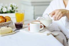 Belle femme derrière une table blanche versant le lait frais dans un chaud Photographie stock