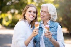 Belle femme deux de sourire mangeant la crème glacée  Images stock
