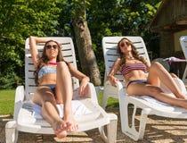 Belle femme deux prenant un bain de soleil sur la plage Photos stock