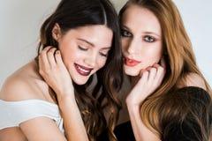 Belle femme deux sexy avec le maquillage lumineux sur un fond blanc Sourire d'amies Émotions positives, bonheur, joie Image libre de droits