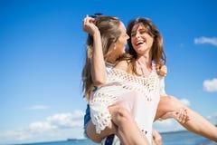 Belle femme donnant à son ami le ferroutage riant dehors Image stock
