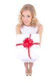 Belle femme drôle jugeant le boîte-cadeau d'isolement sur le blanc Images libres de droits