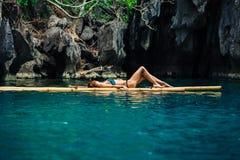 Belle femme détendant sur le radeau dans la lagune tropicale Photos stock
