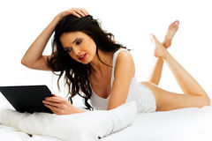 Belle femme détendant sur son lit avec un comprimé Image stock