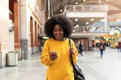 Belle femme employant le mobile dans la station de train Photo stock