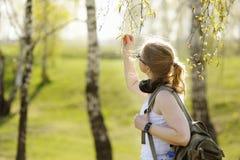Belle femme en ce qui concerne des branches des arbres Photographie stock