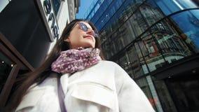 Belle femme en gros plan moyenne de mode dans des lunettes de soleil entourées par le gratte-ciel en verre moderne banque de vidéos