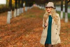 Belle femme en stationnement d'automne fond de jardin d'érable d'ellow regard à la gauche du cadre vers l'espace vide de copie Image stock