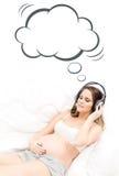 Belle femme enceinte écoutant la musique Image stock