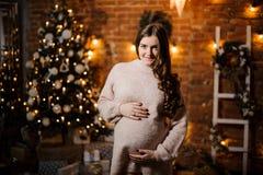 Belle femme enceinte avec de longs cheveux contre l'arbre de Noël Photos libres de droits